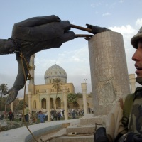 © GORAN TOMAŠEVIČ, Reuters: Americký námořník sleduje svržení sochy iráckého prezidenta Saddáma Husajna na náměstí Firdaus vcentru Bagdádu Irák, 9. 4. 2003 / Member of US Marine Corps watches as the statue of Iraqi president Saddam Hussein is pulled down at Firdaus Square in central Baghdad, Iraq, 9 April 2003