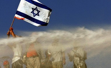 © GORAN TOMAŠEVIČ, Reuters:Demonstrant s izraelskou vlajkou v palbě vodního děla, Gaza 18. 8. 2005 / Demonstrator holding an Israeli flag in the line of water cannon, Gaza, 18 July 2005