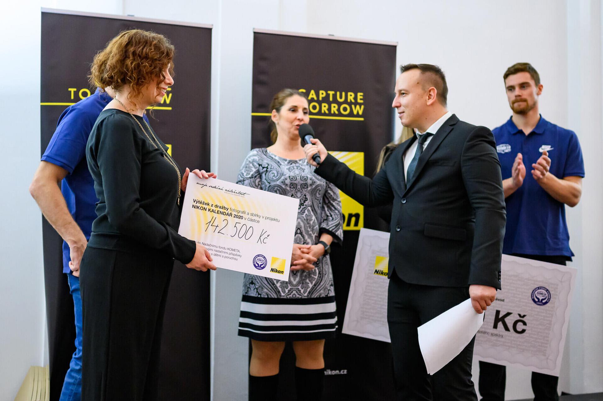 Šek z dražby soutěžních fotografií odevzdává Nadačnímu fondu Kometa PR manažerka Nikonu Jitka Spoustová | Zdroj foto Nikonblog.sk