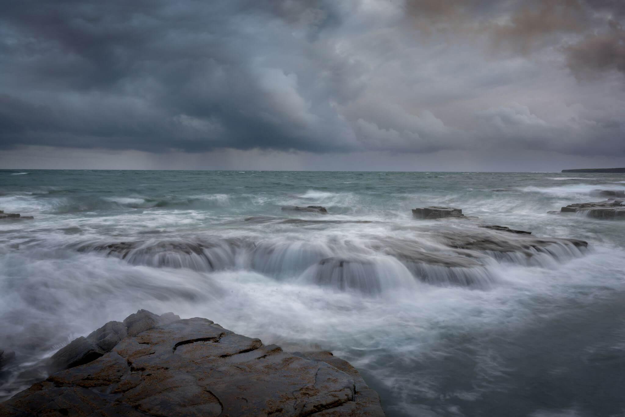 Zvolte vhodnou rychlost závěrky –vlny oceánu obtékající skály s šedými bouřkovými mraky na obloze. Foto George Karbus. Čas 1/3 s, clona F22, ISO 31, ohnisko 33 mm