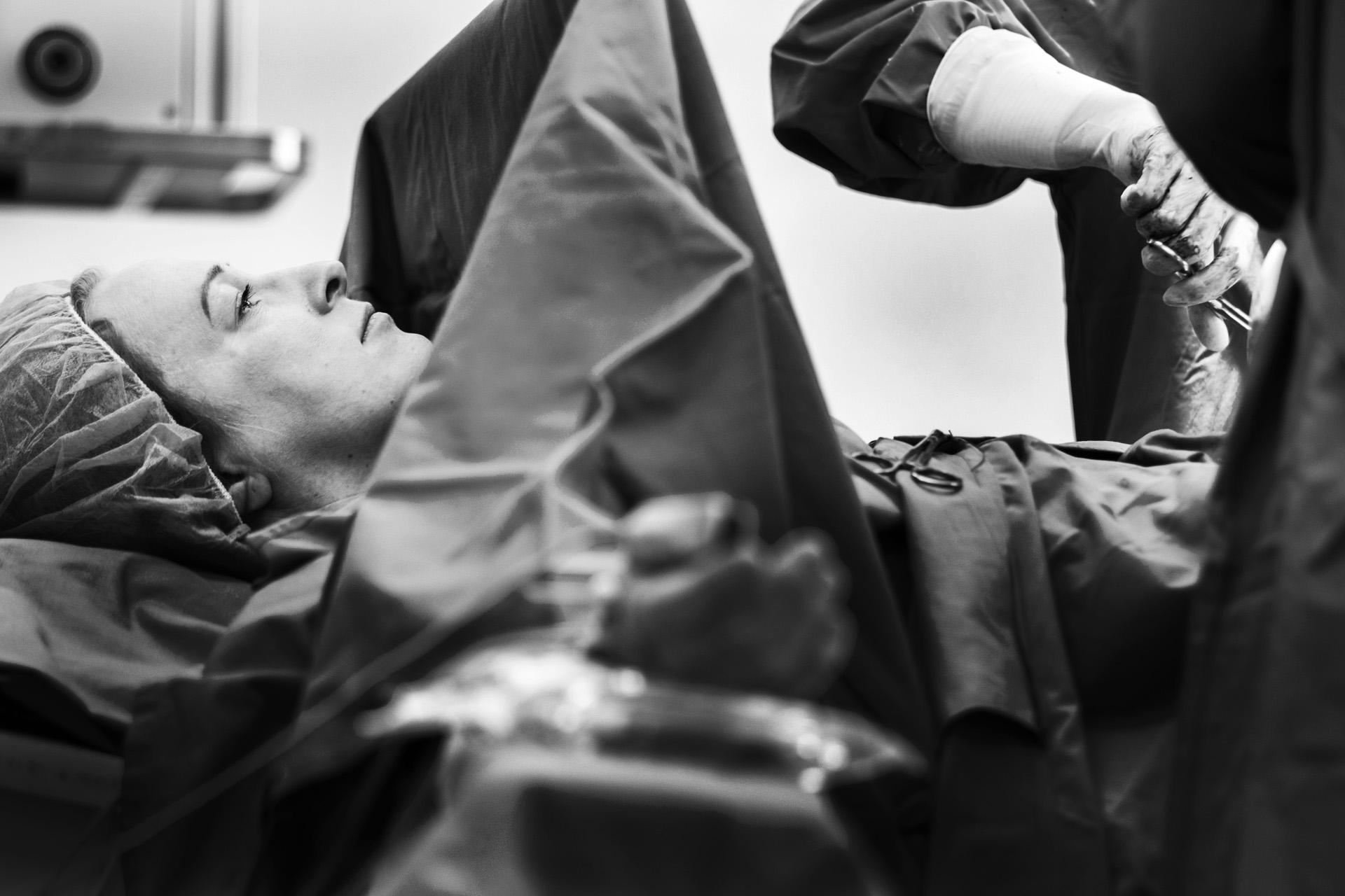 Tina | Po cisárskom reze. Dievčatko už bolo na svete a v opatere zdravotného personálu. Matka ešte leží na stole, v jej tvári sa po dlhých deviatich mesiacoch – zatiaľ, čo ju lekári zašívajú – zobrazuje úľava. | Foto Igor Stančík